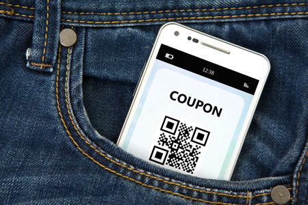 coupon: mobile phone with discount coupon in jeans pocket