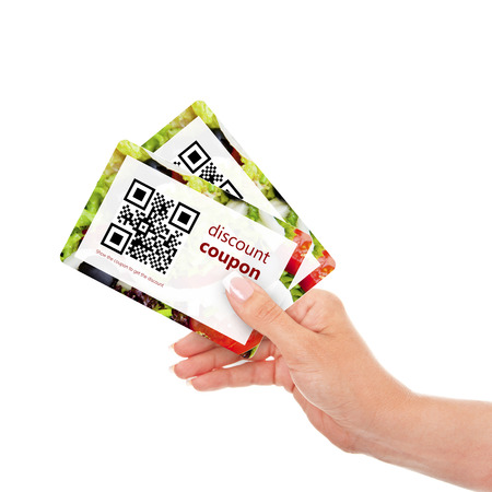 voucher: hand holding two  discount coupons with qr code isolated over white