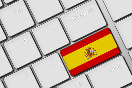 closeup of computer keyboard with spanish flag button photo