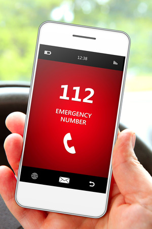 hand holding mobile phone 112 emergency number in car 스톡 콘텐츠