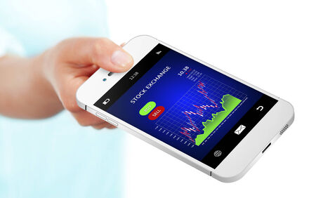 hand holding mobile phone with stock exchange chart over white background photo