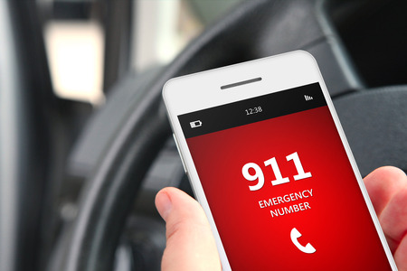 to phone calls: hand holding cellphone with emergency number 911 in car