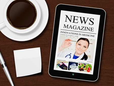 tablet with news magazine, cup of coffee, pen and white sheet lying on wooden desk photo