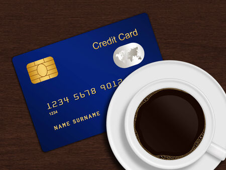 debet: white cup of coffee with credit card lying on wooden desk Stock Photo
