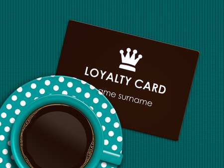 cup of coffee with loyalty card lying on tablecloth Stock Photo