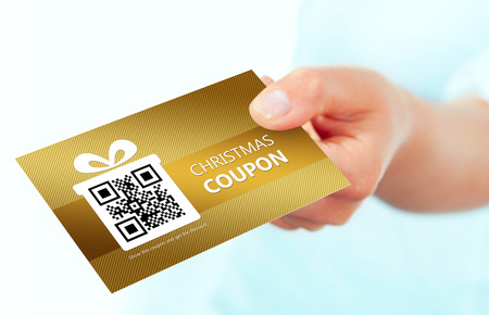 gold christmas coupon holded by hand over white background. focus on coupon.