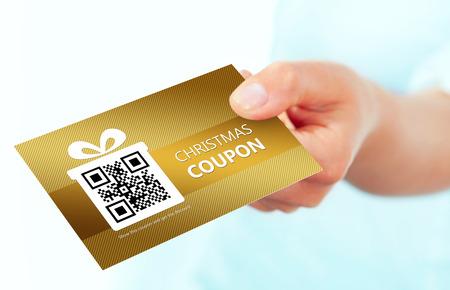 Gouden Kerstbon coupon gehouden met de hand over witte achtergrond. focus op coupon. Stockfoto