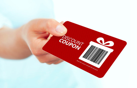 voucher: gold christmas coupon holded by hand over white background. Stock Photo