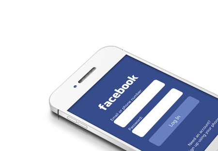 Gdansk, Poland - March 2, 2015: white mobile phone with facebook social network isolated over white background 報道画像