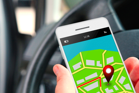hand holding mobile phone with gps application in the car