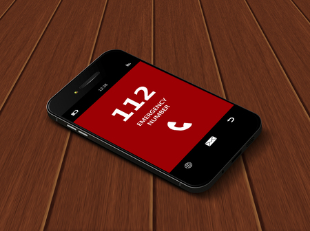 emergency number: mobile phone with emergency number 112  lying on wooden table