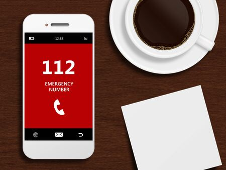 emergency number: mobile phone with emergency number 112 lying on wooden desk Stock Photo