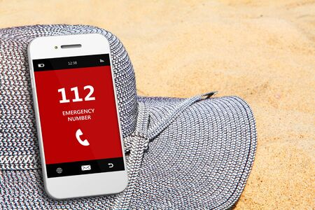 emergency number: mobile phone with emergency number 112  on the beach. focus on screen Stock Photo