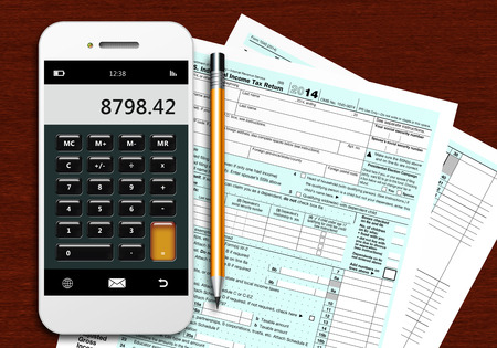 federal tax return: tax form 1040 with phone calculator and pencil lying on wooden table