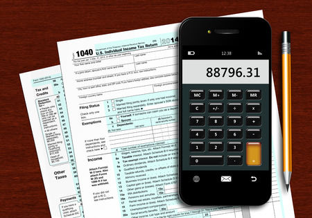 tax return: u.s. individual income tax return form 1040 with phone calculator and pencil lying on wooden table Stock Photo