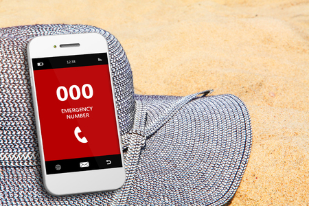 emergency number: mobile phone with emergency number 000 on the beach. focus on screen