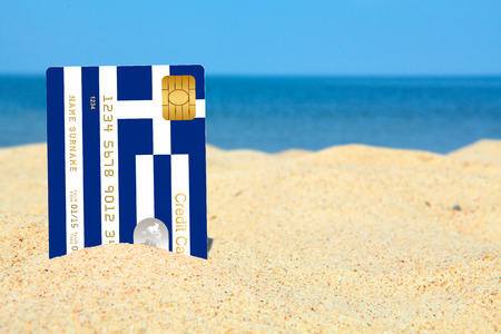 credit crisis: greek credit card on the beach. sky and sea as a background Stock Photo