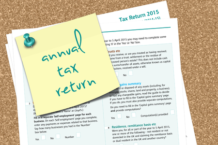 the settlement: SA100 tax form with note anuual tax return text pinned to pin board Stock Photo