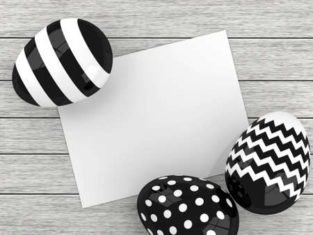 chit: black and white Easter eggs lying on wooden desk with empty stick note