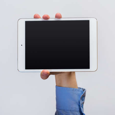 info business: White tablet pc in hands over gray background