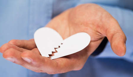 Close up of hand with broken paper heart