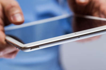 Close up of man hands holding white tablet pc photo