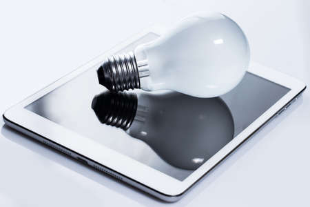 Close up of light bulb and white tablet pc Stock Photo