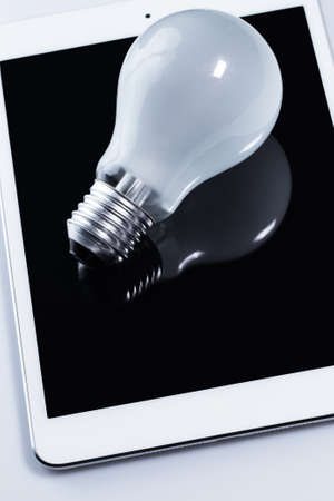 Close up of light bulb and white tablet pc Stock Photo - 24451093