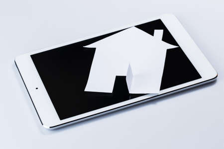 White tablet pc and paper house Stock Photo