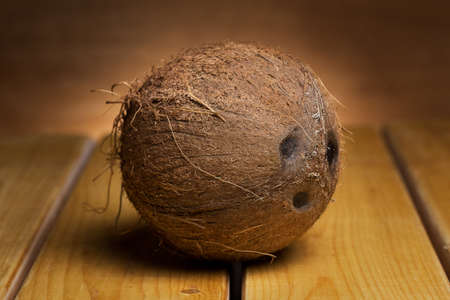 Whole fresh coconut over wooden background photo