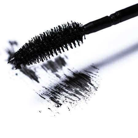 Closeup of mascara brush over white background photo