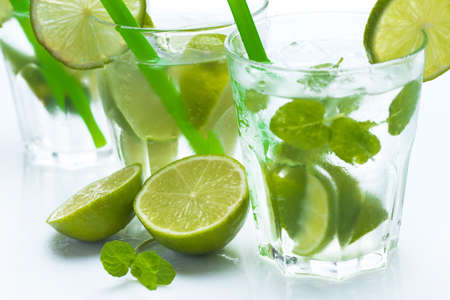 Fresh drink with lime and mint on white background photo
