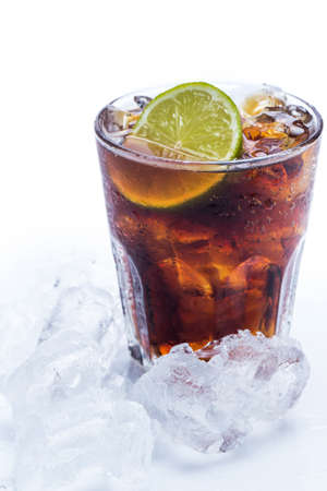 Fresh cocktail with cola drink and lime over white photo