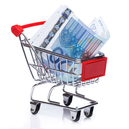 Banknotes in small shopping trolley over white background Stock Photo