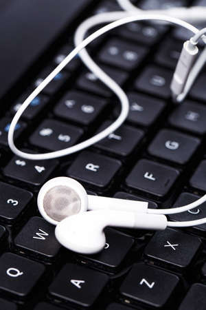 Earphones over laptop keyboard photo