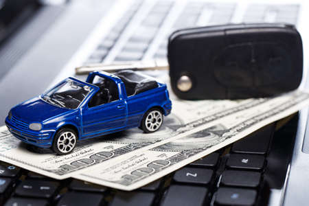 Toy car and banknotes over laptop keyboard photo
