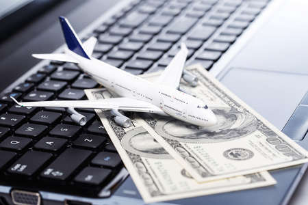 Aircraft and banknotes above laptop Stock Photo