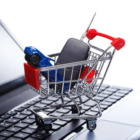 Car and key in shopping trolley above laptop keyboard photo