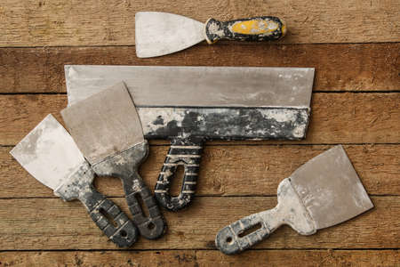 putty knives: Kit of putty knives over wooden table Stock Photo