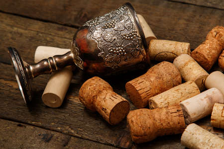 grail: Medieval goblet and wine corks on wooden table Stock Photo