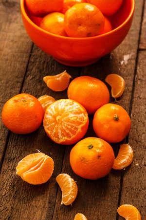 Fresh mandarins in bowl on wooden table