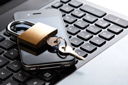 Smartphone and padlock is lying on a laptop keyboard photo