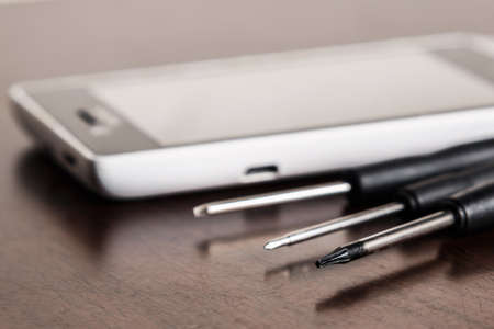 Smartphone and small screwdrivers on wooden table