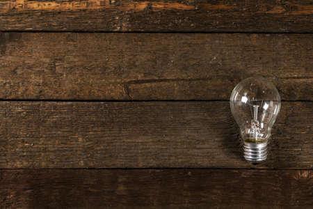 Old lightbulb on wooden background photo
