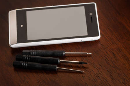 screwdrivers: Smartphone and small screwdrivers on wooden table
