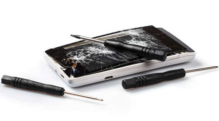 screwdrivers: Smartphone with cracked display and screwdrivers