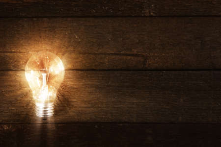 unique: Glowing lightbulb on wooden background Stock Photo