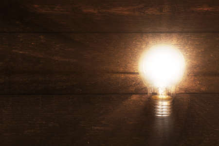 Glowing lightbulb on wooden background photo