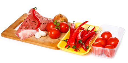 Raw meat and vegetables on chopping board