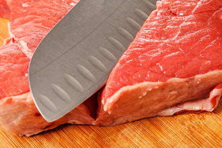 Knife and meat on chopping board photo